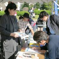 Former abductee Hitomi Soga (left) collects signatures at an event Sunday on Sado Island in the Sea of Japan to call for the prompt return of her fellow abductees from North Korea. Soga was abducted in 1978 but was allowed to return with four other Japanese in 2002. | KYODO