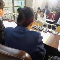 A female official suing the government over denial of promotion because of her gender speaks to journalists Tuesday after filing the lawsuit with the Tokyo District Court. | KYODO