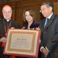 Japanese conductor Tomomi Nishimoto (center) is honored at the Vatican music festival in Rome on Thursday. | KYODO