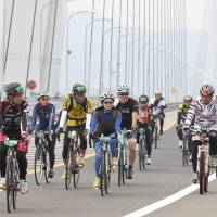 Cyclists cross the Tatara Bridge on the Nishiseto Expressway, commonly known as Shimanami Kaido, during the Cycling Shimanami event Sunday. | KYODO