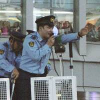 A policeman later nicknamed 'DJ cop' for his witty crowd control skills speaks to soccer fans in Shibuya, Tokyo, on June 4, 2003, after Japan qualified for the 2014 World Cup.