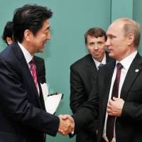 Prime Minister Shinzo Abe and Russian President Vladimir Putin chat briefly Oct. 17 in Milan on the sidelines of the Asia-Europe Meeting summit. | CABINET OFFICE/KYODO.