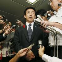 Health minister Yasuhisa Shiozaki responds to reporters' questions Monday night after a man arriving at Haneda airport in Tokyo was hospitalized and undergoing a test for Ebola. | KYODO