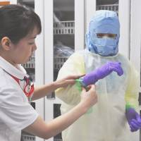 Nagasaki University Hospital nurses on Wednesday practice donning the kind of protection needed for Ebola. | KYODO