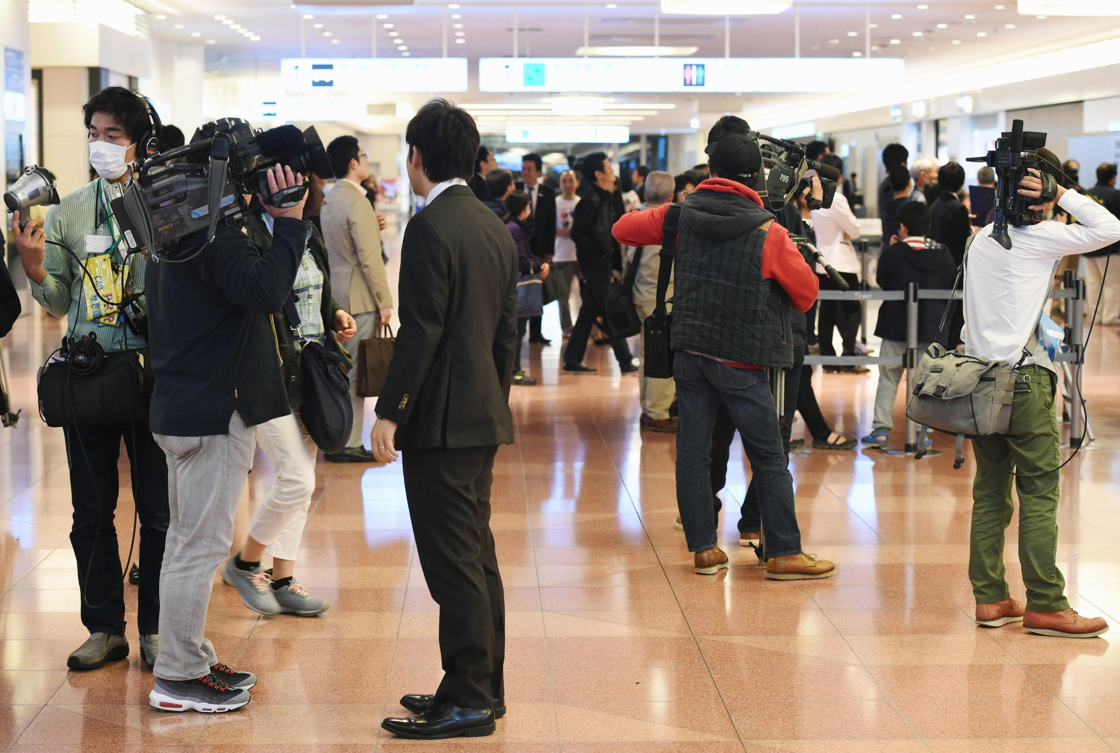 Journalists gather in an arrival lobby at Tokyo's Haneda airport Monday night. | KYODO