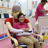 An UniCare employee demonstrates the 'yasuragi' (tranquility) chair at the International Home Care and Rehabilitation Exhibition in Tokyo on Wednesday. The chair's arms are joined with fabric fastening tape and can hug users. | AFP-JIJI