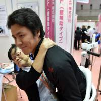 A Cyberdyne employee carries a woman during a demonstration of the nursing version of the Hybrid Assistive Limb (HAL), a robot suit developed by University of Tsukuba professor Yoshiyuki Sankai, at the annual International Home Care and Rehabilitation Exhibition in Tokyo on Wednesday. The HAL can learn from and adapt to people's movements for use in nursing homes or hospitals. | AFP-JIJI