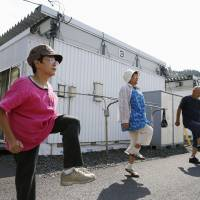 Elderly disaster evacuees in the town of Otsuchi, Iwate Prefecture, exercise to NHK Radio's calisthenics music in September. The sports ministry's fiscal 2013 survey on physical fitness, released ahead of Sports Day on Monday, said elderly women are at the top of their game. | KYODO