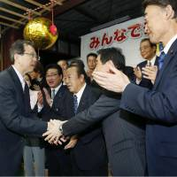 Fukushima Gov.-elect Masao Uchibori (left) is congratulated Sunday by supporters, including Takumi Nemoto (right), a Liberal Democratic Party lawmaker. Uchibori has served as vice governor for the best part of a decade.   KYODO