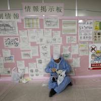 A worker prepares for work in front of an information board inside the emergency operation center at Tokyo Electric Power Co.'s tsunami-crippled Fukushima No. 1 nuclear power plant in Fukushima Prefecture in February 2012. Almost a year after Japan pledged to double hazard pay at the stricken plant, workers are still in the dark about how much extra they are getting paid, if anything, for cleaning up the worst nuclear disaster since Chernobyl. | REUTERS