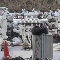 Workers build an underground frozen wall at Tokyo Electric Power Co.'s tsunami-crippled Fukushima No. 1 nuclear power plant in Fukushima Prefecture in March. Almost a year after Japan pledged to double hazard pay at the stricken plant, workers are still in the dark about how much extra they are getting paid, if anything, for cleaning up the worst nuclear disaster since Chernobyl. | REUTERS