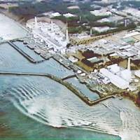 An aerial photo taken by the land ministry shortly after the March 11, 2011, earthquake shows tsunami reaching the Fukushima No. 1 nuclear plant.  | LAND MINISTRY/KYODO