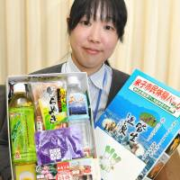 An official from Yonago, Tottori Prefecture, displays a box of local delicacies that donors receive for making tax-deductible contributions to the city. | KYODO