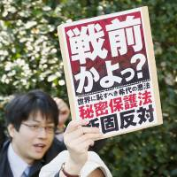 A woman protests against the state secrets law at a rally in the city of Osaka in December 2013, brandishing a placard that roughly translates as: 'Is this pre-World War II? We oppose the singularly ill-thought-out and shameful state secrets law.' | KYODO
