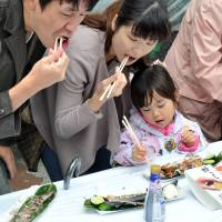 Parents and a child tuck into some grilled saury at the annual Meguro 'sanma' festival on Sept. 7. | YOSHIAKI MIURA