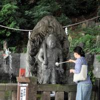 A woman pours water before a statue of the god of fire at Meguro Fudo Temple on Sept. 17. | YOSHIAKI MIURA