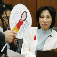 Justice Minister Midori Matsushima (right) is questioned in the Lower House on Oct. 15 about her distribution of 'uchiwa' fans in her electoral district, an action the Democratic Party of Japan alleged constituted a violation of the election campaign law. Matsushima resigned her Cabinet post Monday. | KYODO
