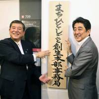 Regional revitalization minister Shigeru Ishiba (left) and Prime Minister Shinzo Abe display a sign in front of Ishiba's new office in Tokyo on Sept. 5. | KYODO