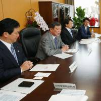 Regional revitalization minister Shigeru Ishiba (second from left) speaks with officials of a nonprofit organization that is supporting the relocation of people to provincial areas, in Tokyo on Oct. 2. | POOL/KYODO