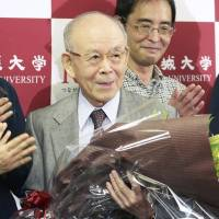 Professor Isamu Akasaki is congratulated by some of his students at Meijo University in Nagoya on Tuesday after he was named one of the winners of this year's Nobel Prize in physics. | KYODO