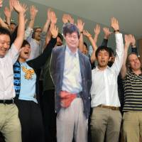 Nagoya University students shout 'banzai' with a life-size photo of professor Hiroshi Amano in Nagoya on Tuesday after he was named one of this year's winners of the Nobel Prize in physics. | KYODO