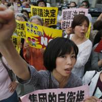 Protesters hold a rally in front of the prime minister's office in Tokyo on June 26 against Prime Minister Shinzo Abe's push to reinterpret the war-renouncing Constitution. | AP