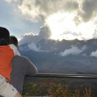 A father and his son look toward Mount Ontake in the town of Kiso, Nagano Prefecture, on Sunday, the day before the one-month aniversary of the volcano's deadly eruption Sept. 27. | KYODO