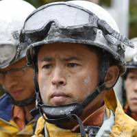 Firefighters engaged in search operations pause Thursday in Otaki, Nagano Prefecture. Rescue crews have repeatedly suspended operations amid volatile conditions on the summit, including rain that is posing a risk of ash-triggered mudslides. | KYODO