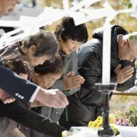 People pray for victims of the Sept. 27 eruption of Mount Ontake during a memorial service in the village of Otaki, Nagano Prefecture, on Monday. | KYODO