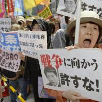 A woman protests the Cabinet's move to reinterpret the Constitution to allow the use of collective self-defense to help allies under attack, in Tokyo on July 1. | KYODO