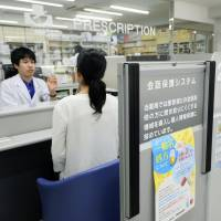 Loudspeakers are attached to partitions at Ebira Pharmacy in Kobe, Hyogo Prefecture, on Aug. 20. The system helps to prevent people from overhearing conversations in the booth behind.   KYODO