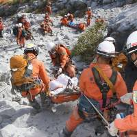 Tokyo Fire Department rescue workers carry injured hikers down Mount Ontake on Sunday. | TOKYO FIRE DEPARTMENT/KYODO