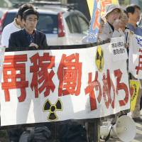Anti-nuclear protesters stage a rally Tuesday outside City Hall in Satsumasendai, Kagoshima Prefecture, before the municipal assembly voted in favor of restarting Kyushu Electric Power Co.'s Sendai nuclear plant. | KYODO