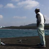 A fisherman gazes at the two reactors of Kyushu Electric Power Co.'s Sendai nuclear plant in Satsumasendai, Kagoshima Prefecture, on Monday. | BLOOMBERG