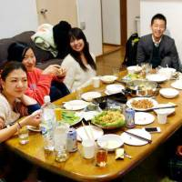 Students and residents interact during a meal in a shared housing complex run by Come on UP Co. | KYODO