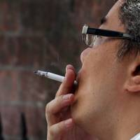 A man smokes in a designated smoking area in Tokyo. Lawmakers are reportedly planning to launch a suprapartisan group with the aim of establishing a new law to prevent secondhand smoke in public spaces toward the 2020 Tokyo Olympics. | BLOOMBERG
