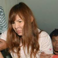 Escorted by Thai police, murder suspect Phornchanok Chaiyapa is taken to the scene of the murder of Japanese teacher Yoshinori Shimato near Bangkok on Saturday. Her ex-husband Somchai Kaewbangyang, also arrested over the slaying, has reportedly confessed to killing another Japanese man. | KYODO