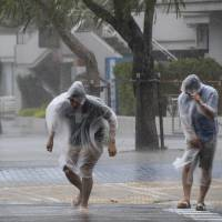 People brave driving rain in Naha, Okinawa Prefecture, on Saturday as Typhoon Vongfong approached the island. | KYODO