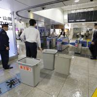 JR officials scramble to collect rainwater leaking through the ceiling at Tokyo Station as Typhoon Phanfone made landfall Monday morning. | KYODO