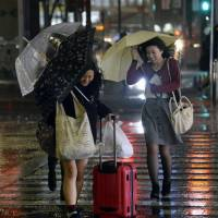 Pedestrians brave the storm near Nagoya Station on Monday night. Typhoon Vongfong caused massive rail and air travel disruption and prompted widespread evacuation advisories. | KYODO