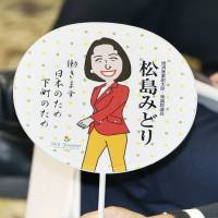 A lawmaker brandishes one of Justice Minister Midori Matsushima's contentious 'uchiwa' (fans) on Oct. 7 at an Upper House committee meeting. | KYODO