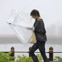 A woman shields herself with a mangled umbrella Monday afternoon as she navigates a road during Typhoon Vongfong in Kochi Prefecture. | KYODO