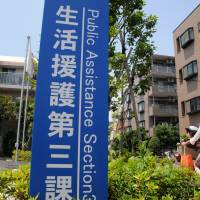 A mother and child ride past a signboard for a public assistance office in Edogawa Ward, Tokyo, on July 25. | SATOKO KAWASAKI