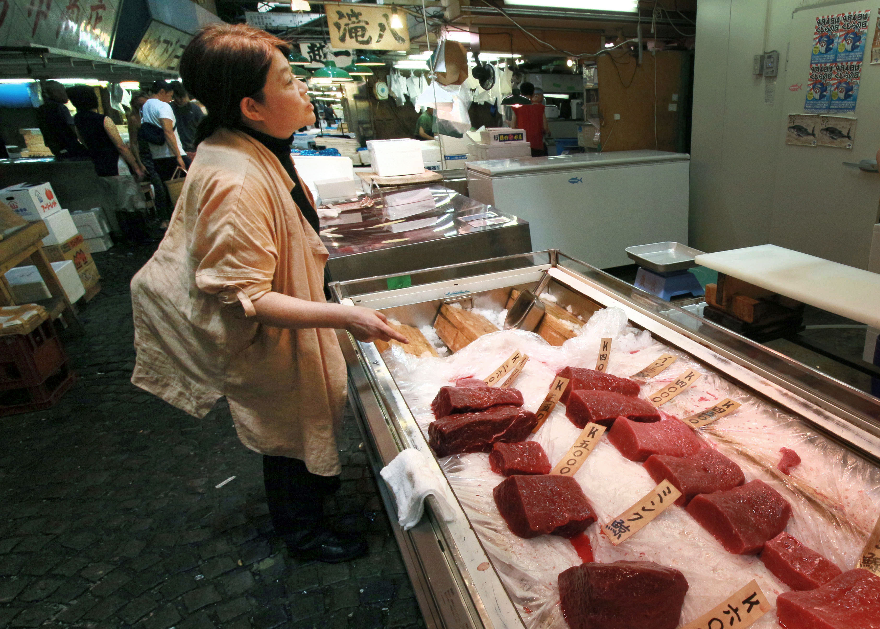 Junko Sakuma visits a store selling whale meat in the Tsukiji fish market in Tokyo on Aug. 5. She says annual consumption in Japan is less than 30 grams per person. | KYODO