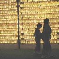 Visitors take in some of the 30,000 paper lanterns illuminated during a festival at Tokyo's Yasukuni Shrine on July 13. A chapter of the Japan War-Bereaved Families Association is asking Yasukuni officials to remove the names of war criminals enshrined there. | REUTERS