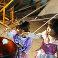 Children dressed up as Disney princesses roast marshmallows at The Third Park in Tokyo. This weekend it will hold a Halloween event with trick-or-treating. | MAI HAYASHI