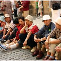Get this show on the road: A group of elderly Japanese tourists sits on a curb, while on holiday in Spain. | MARG / CC BY 2.0