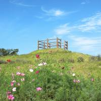 Art with a view: Antony Gormley's 'Another Time' (left) faces eastward, looking into the distance of Kunisaki of Oita Prefecture, while Choi Jeonghwa's 'Iro iro iro' offers visitors a raised platform from which to view the area's multitude of flowers. | MIO YAMADA