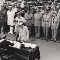 Sign on the dotted line: Foreign Minister Mamoru Shigemitsu signs the unconditional surrender papers for Emperor Hirohito, thus committing Japan to accept the Potsdam Declaration, on Aug. 14, 1945.   AP