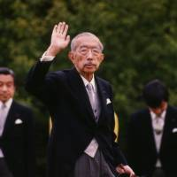 Loyal supporters: Emperor Hirohito waves during a party at the Akasaka Imperial Gardens in Tokyo in May 1988. | AP